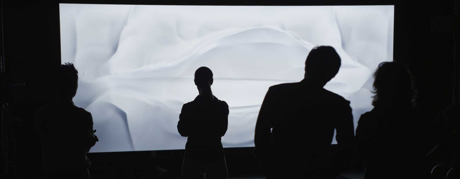 Audience in front of display. Still from Mercedes-Benz Commercial.